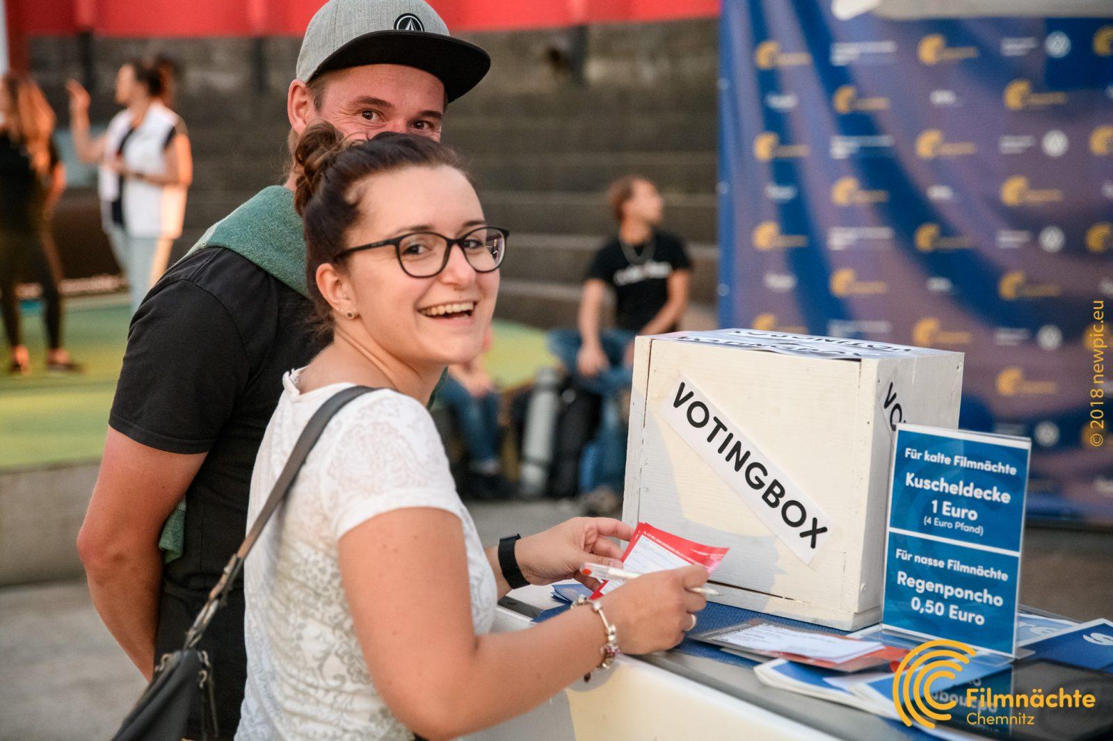 Zwei gut gelaunte Filmnächte-Besucher vor der Voting-Box im Sommer