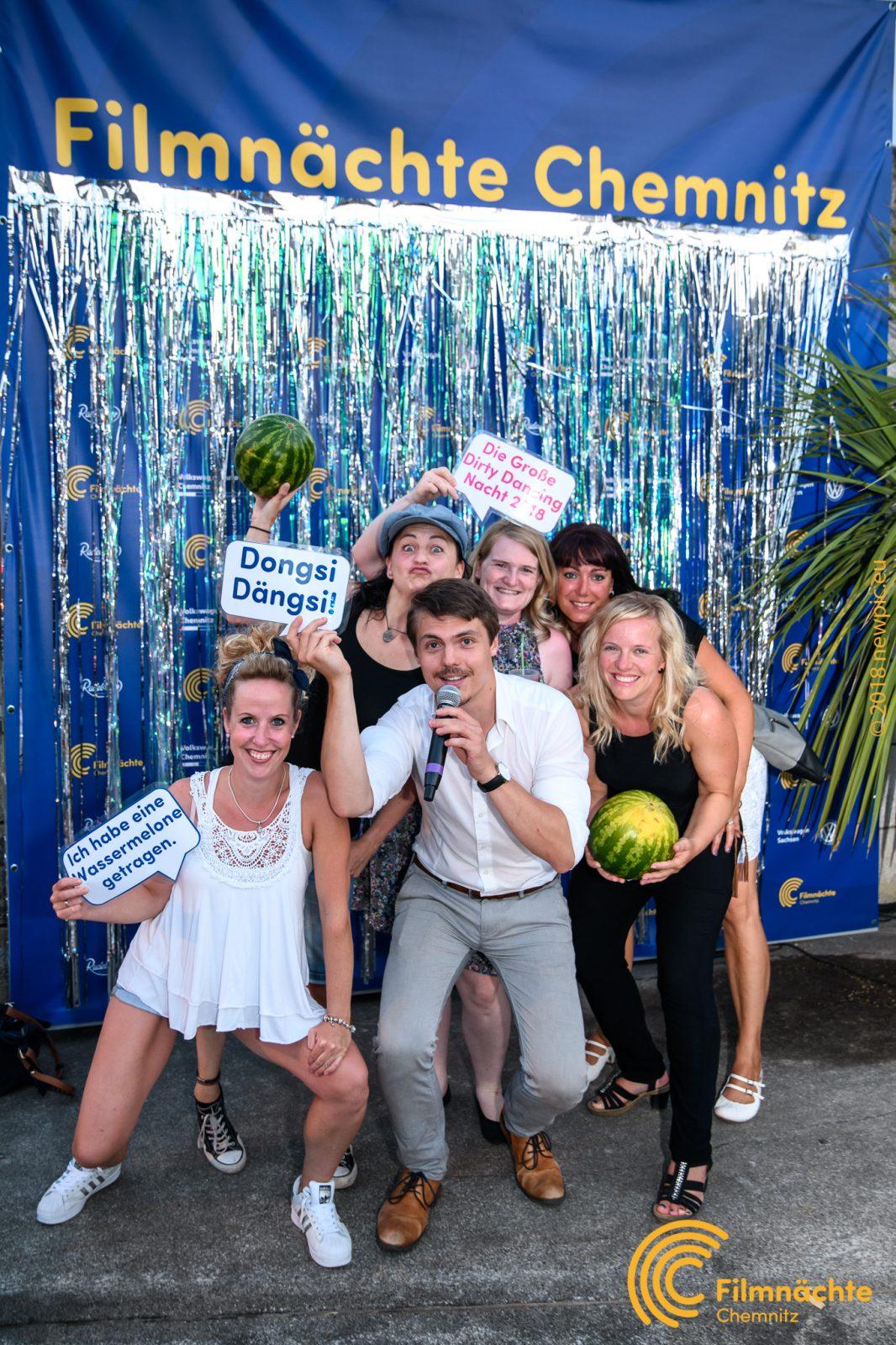 """Gruppenbild vor Filmnächte-Fotowand zu """"Dirty Dancing"""" mit Utensilien wie Wassermelone"""