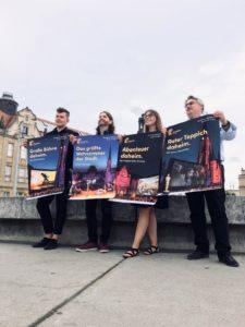Vier Personen präsentieren neue Filmnächte-Werbeplakate zur Programm-Veröffentlichung