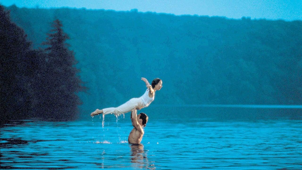 """Filmszene aus """"Dirty Dancing"""": Tanzlehrer hebt Schülerin im Wasser stehend hoch für Hebefigur"""