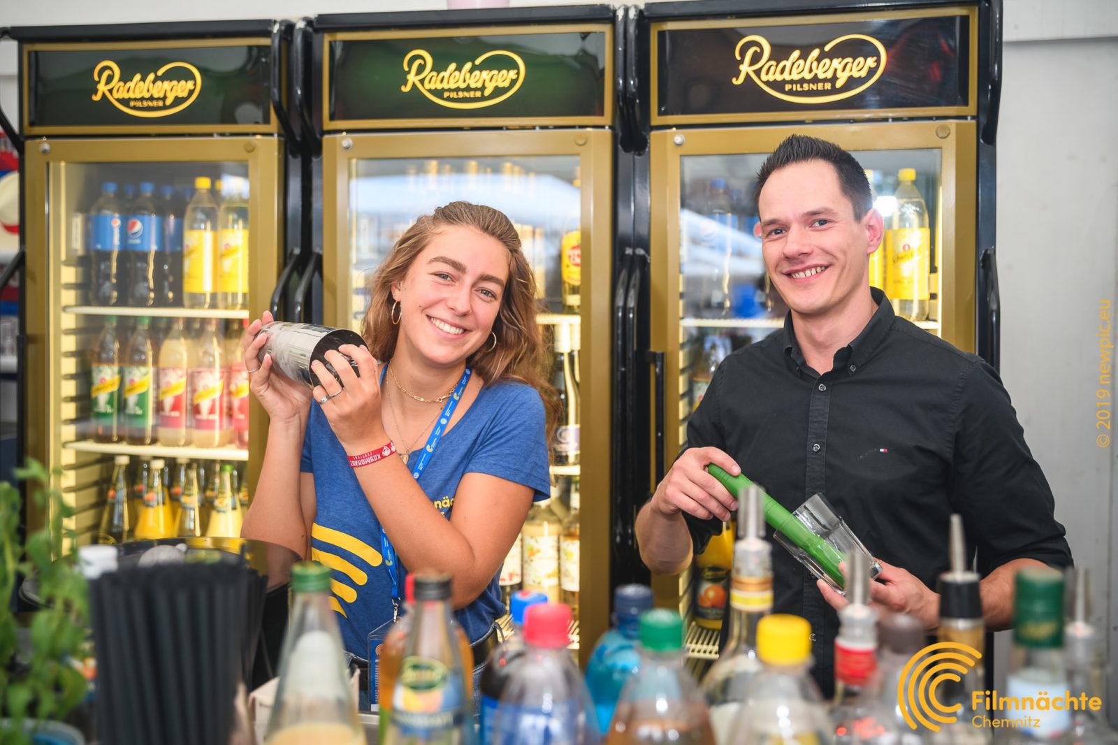 Barpersonal hinter der Theke bereiten Cocktails zu