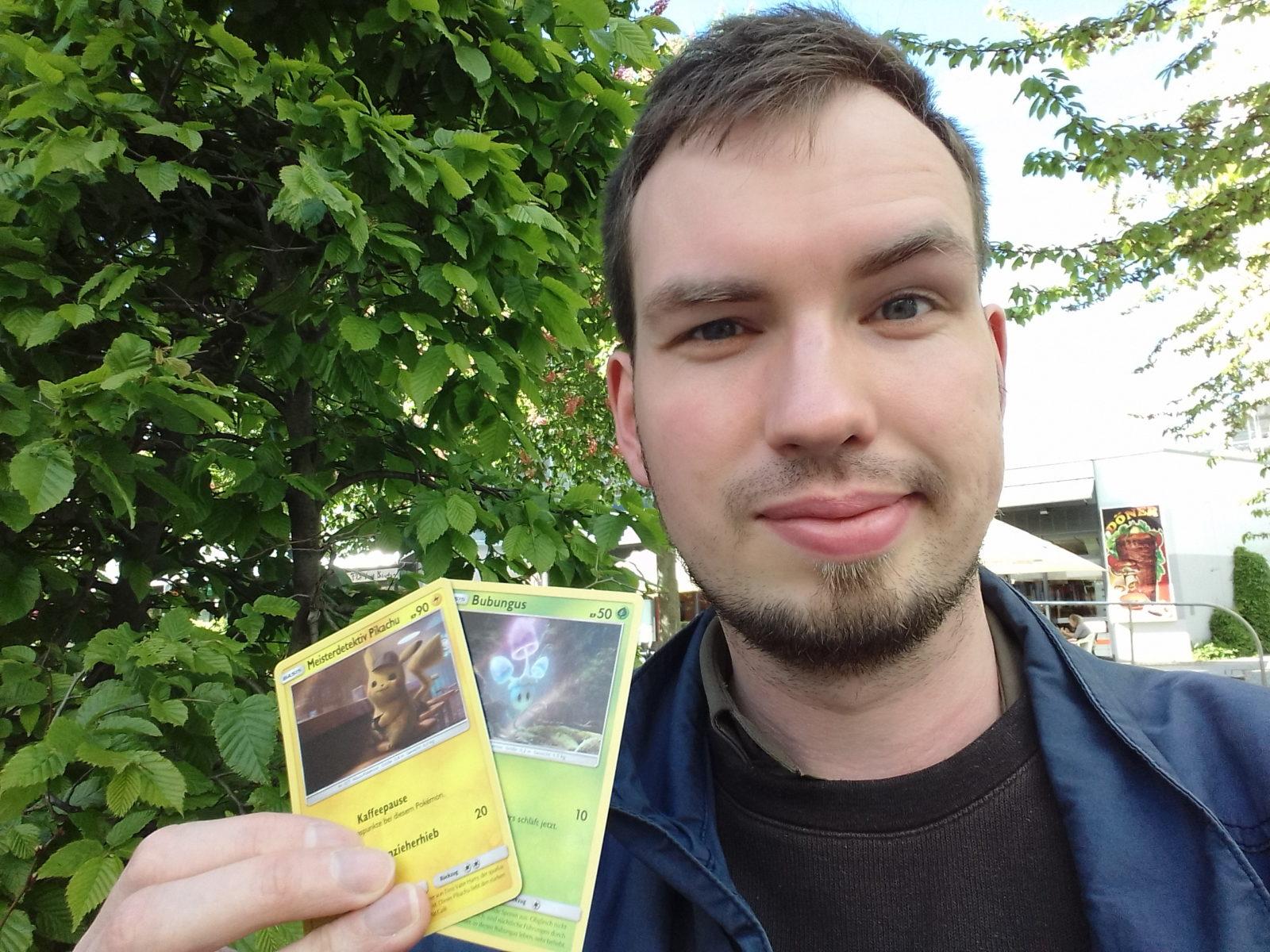 Blog-Autor Jakob mit zwei Pokémon-Sammelkarten, draußen in der Chemnitzer Innenstadt