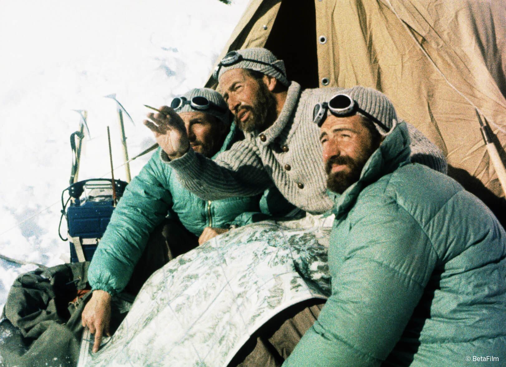"""Filmszene aus """"Nanga Parbat"""" von 1953, drei Bergsteiger mit Landkarte beraten sich"""