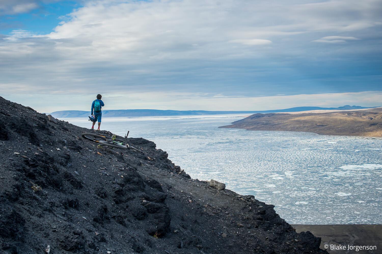 Mann blickt auf weitläufige Gletscher-Gerölllandschaft, sein Mountainbike liegt daneben