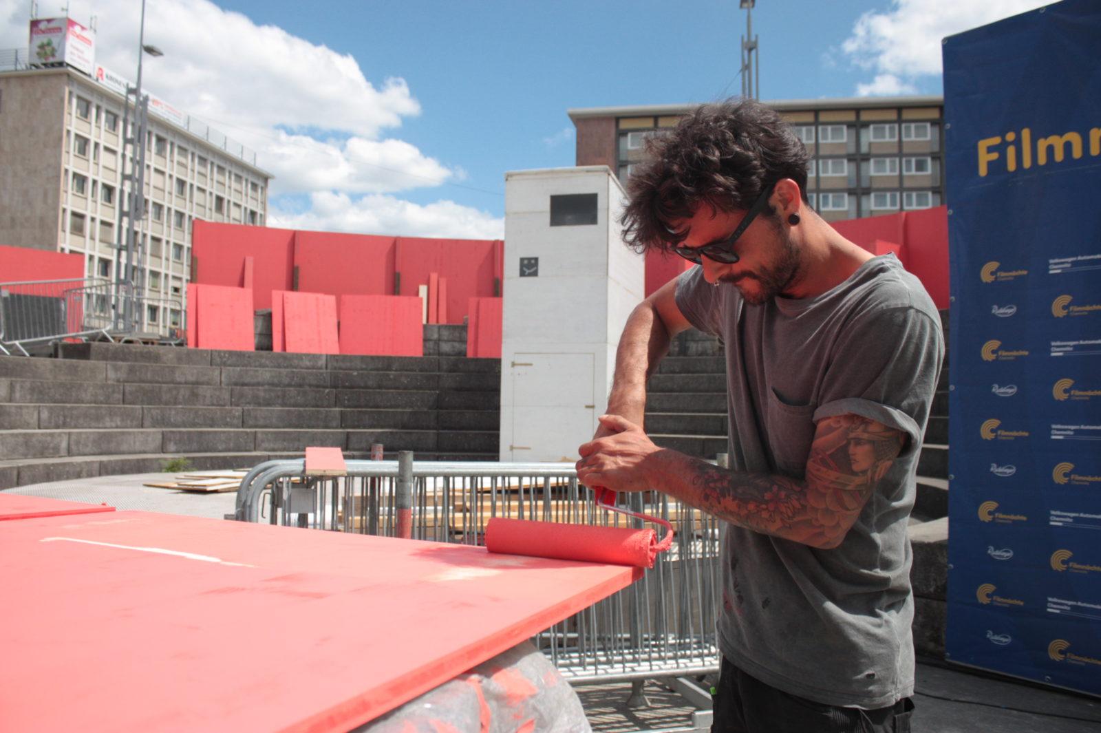 Handwerker malert Holzplatte rot