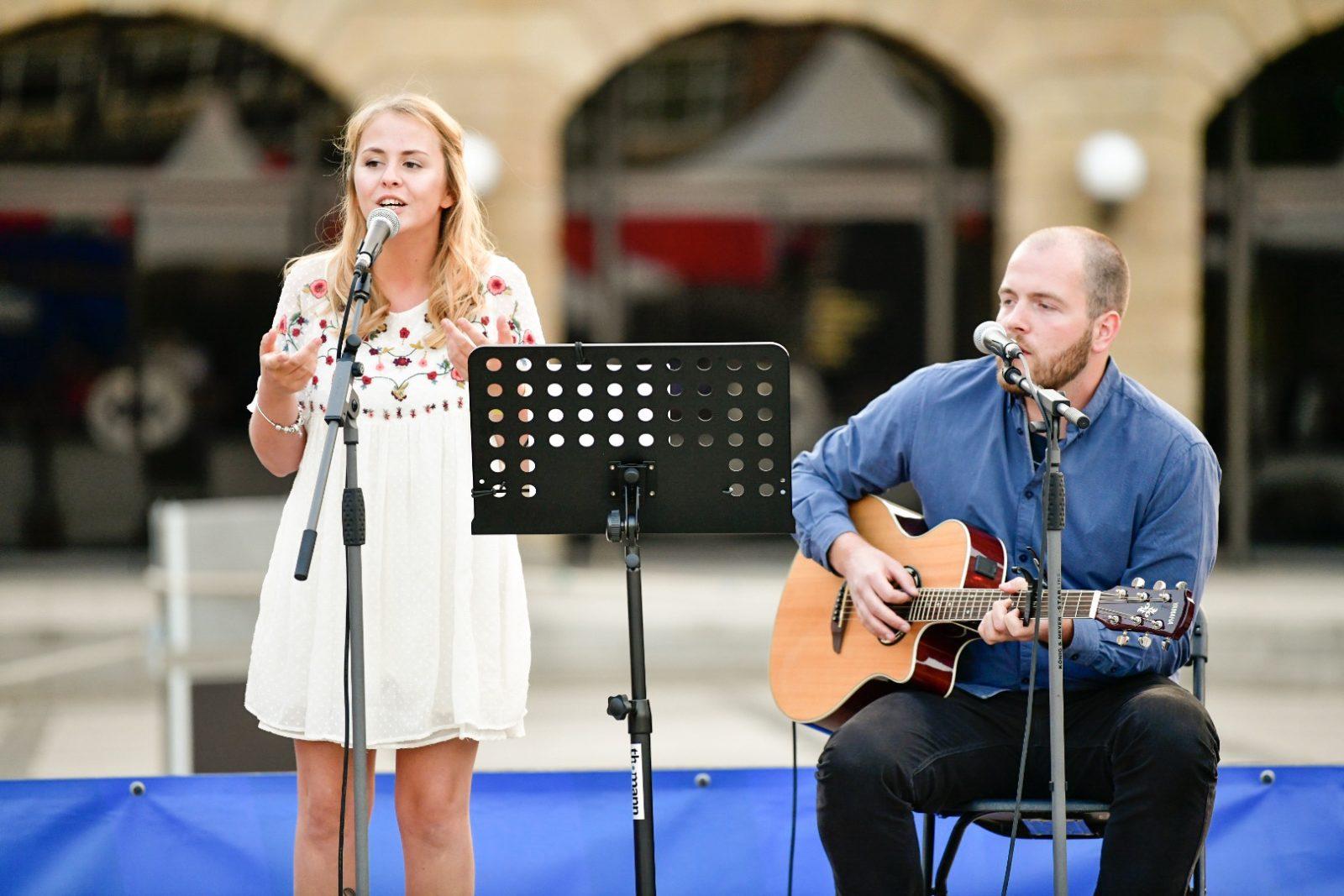 Gesangs-Duo ELMA performt auf der Bühne (Frau am Mikro, Mann an der Gitarre)