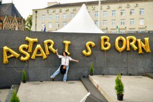"""Besucherin posiert lustig vor """"A Star Is Born""""-Schriftzug mit Luftballons"""