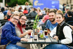 Vier Besucher am Tisch mit Getränken lachen in die Kamera