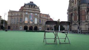 Theaterplatz mit grünem Fußboden, dazu einzelne Stühle